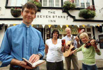 A vicar in front of a pub