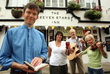 A vicar in front of a pub